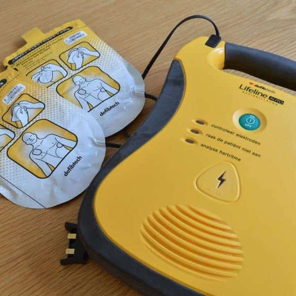 Image of a yellow defibrillator and its pads
