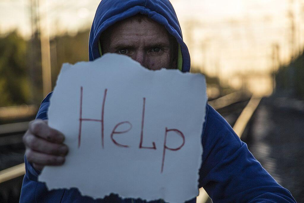 Image of a man holding a sign asking for help