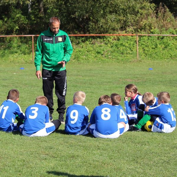 Emergency First Aid for Sport - Image of a sports coach talking to a group of children
