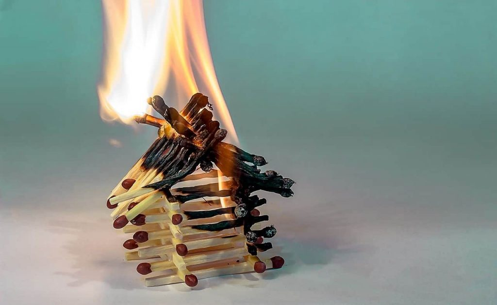 Image of a house made from matchsticks burning.