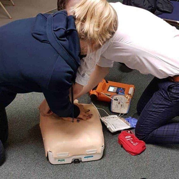 Image showing AED pads being placed on a casualty while receiving CPR