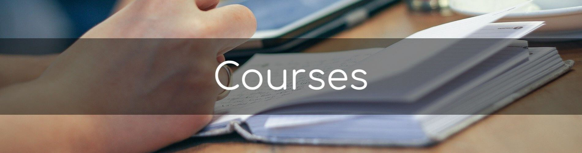 Welcome to our courses page. Image of someone writing notes in a notebook.